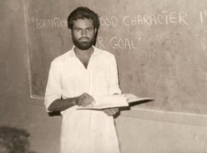 Younus AlGohar teaching a class in Karachi, Pakistan. On the board is written, 'Formation of a good character is our goal.'